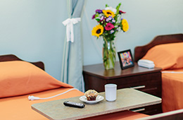 flowers on a bedside table with a muffin and coffee