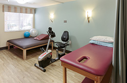 physical therapy area with matted tables and bike