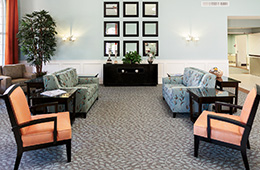 lobby area with sofas, chairs and a carpeted floor