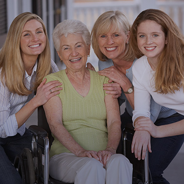 A family of women sitting outside smiling together