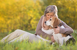 woman seated outside in a meadow on a sunny day with her beagle dog