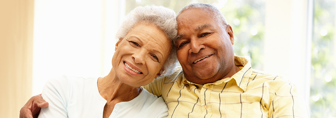 elderly couple seated inside with their heads tilted together