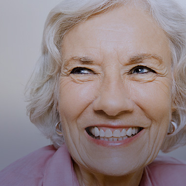 A woman smiling while looking into the distance