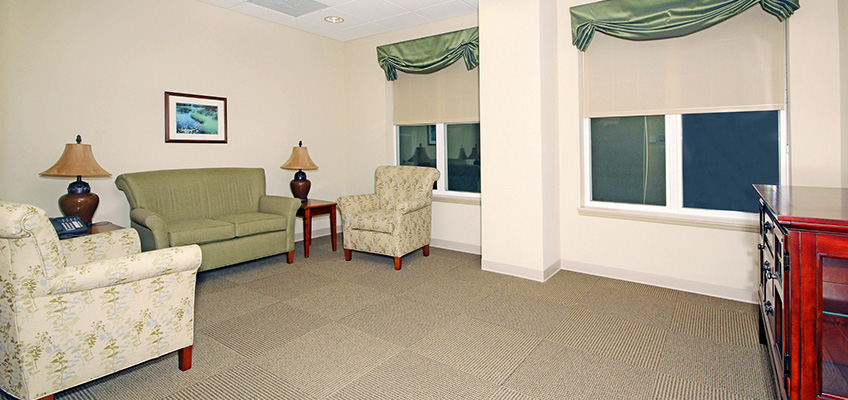A room with couches, chairs and windows