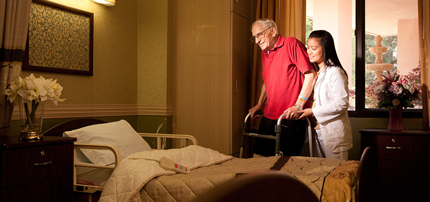 A resident being assisted to his bedside by a staff member