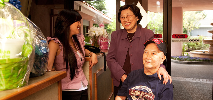 A resident and loved one entering the facility being greeted by a smiling staff member
