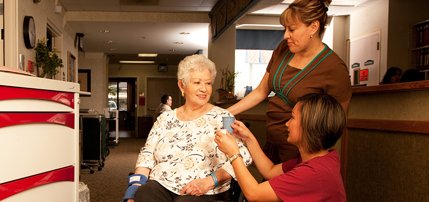 Two staff members caring for a resident with great care