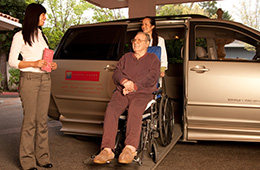 A resident exiting a van in a wheelchair being greeted by a staff member