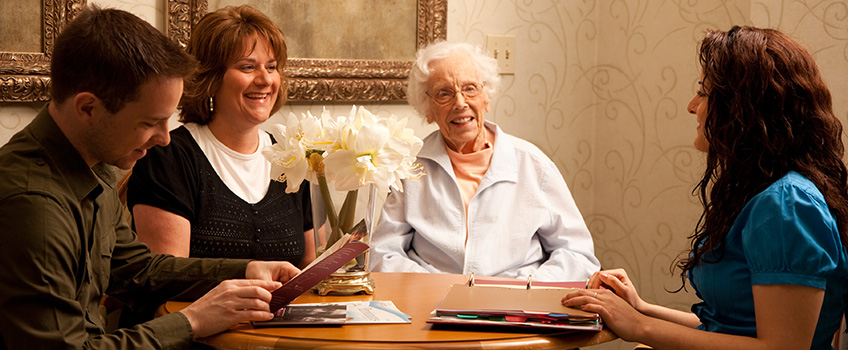 A resident with her loved ones going over paperwork with a staff member