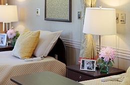 A double occupancy room with images of loved ones on the side table