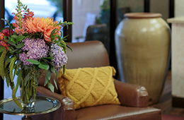 A table with a beautiful vase of flowers next to an inviting chair