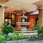 Front entrance of the building with large pillars and a beautiful large waterfall