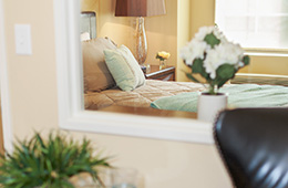 single bed with decorative pillows and night table
