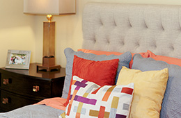 bed with decorative pillows and nightstand