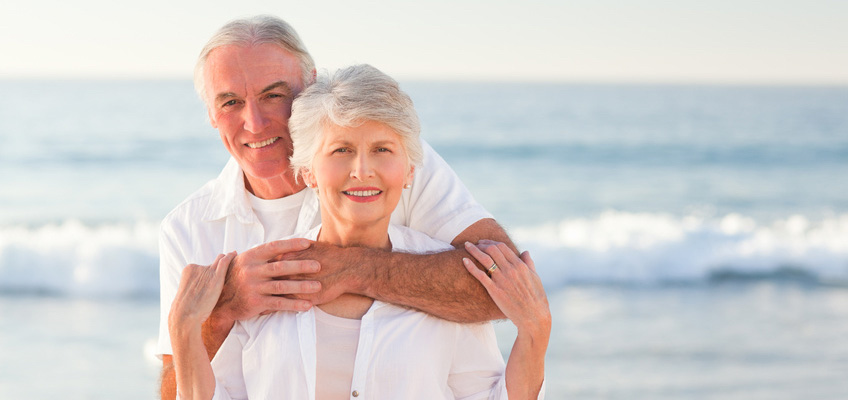 smiling older couple, embracing on the beach with waves in the background