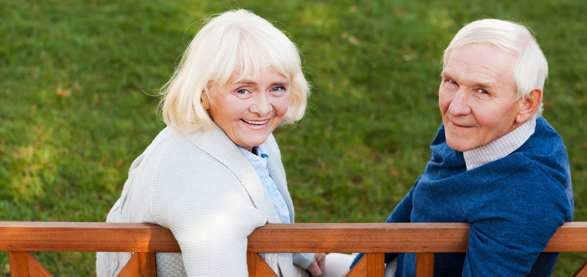 smiling elderly couple sitting on a park bench