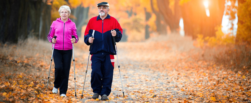 couple hiking with poles and autumn leaves everywhere