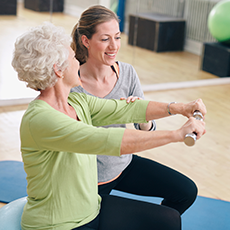 female resident working out with a trainer using small hand weights