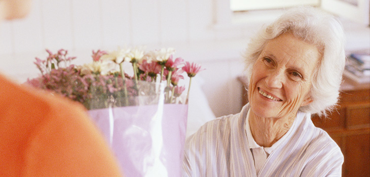 smiling elderly woman receiving a bouquet of flowers