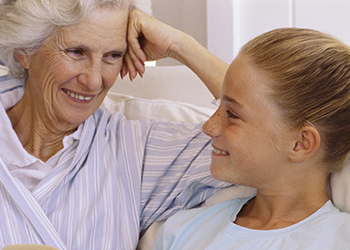 woman smiling fondly at her young granddaughter
