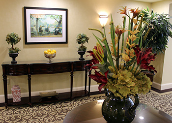 carpeted hallway with artwork and flower arrangements on display