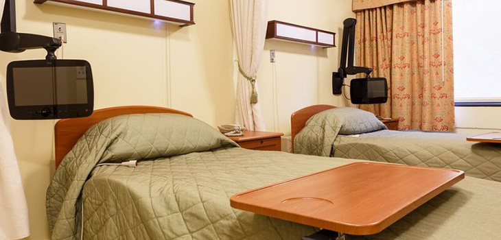 double occupancy room with personal tvs at each bed