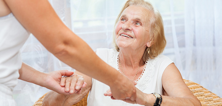 patient smiling while getting a hand up from a nurse