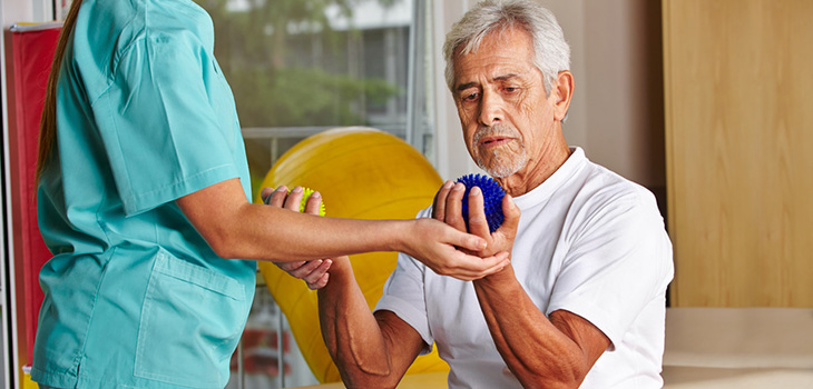 silver haired gentleman working with squeeze ball therapy equipment