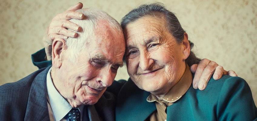elderly couple hugging in old fashioned clothes