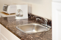 close up on a sink in the kitchen with a coffee maker in the background