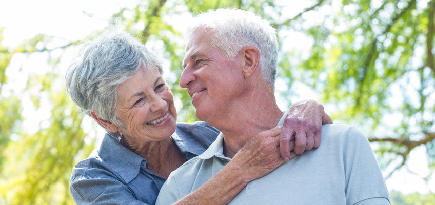 elderly couple smiling at each other with trees in the background