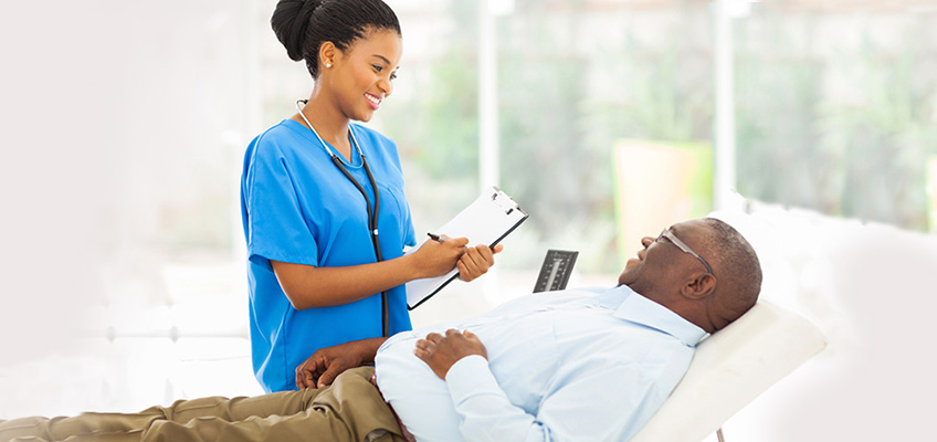 nurse talking to a man that is laying down
