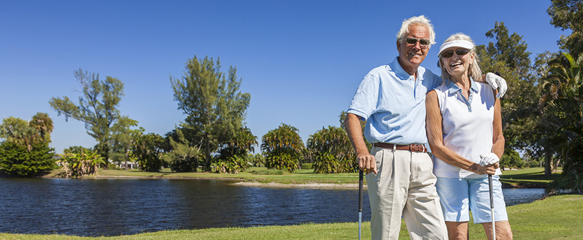 elderly couple playing golf with a lake and trees in the background