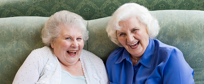 two white haired ladies sitting on a couch laughing