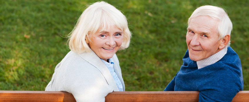elderly couple sitting on a park bench smiling