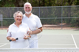 older couple wearing white and playing tennis