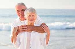older couple wearing white, hugging by the beach