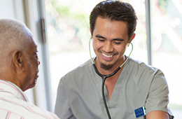 smiling male nurse with a stethoscope helping and older man