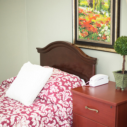 table with patterned sheets and a phone on the bedside table