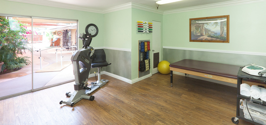 rehab room with various pieces of equipment and large sliding glass door