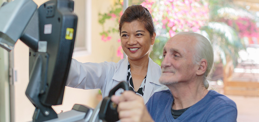 elderly man on an arm bike for physical therapy and a woman doctor