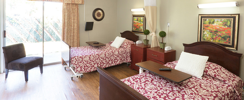 nice looking two bed room with patterned sheets and paintings