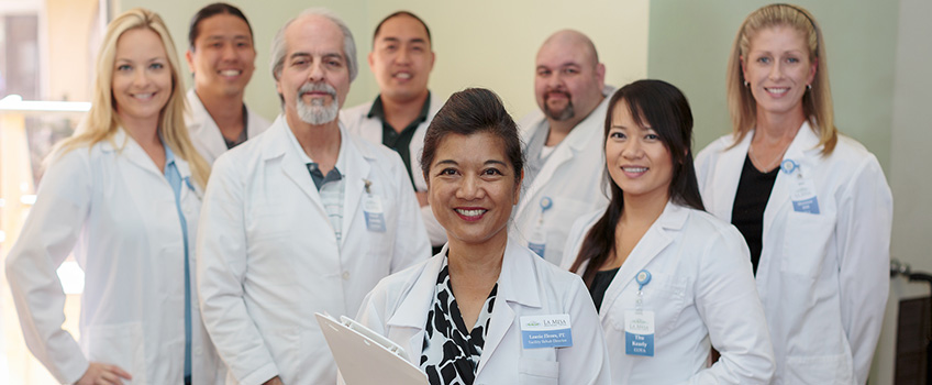 staff photo shot with 8 people in doctors coats