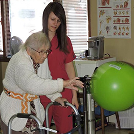 A resident performing rehabilitation exercises with a staff member