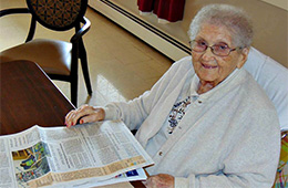 Resident smiling while reading the newspaper
