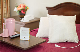 pillows on a bed with a thermos and paper welcome sign