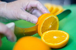 oranges being cut on a cutting board