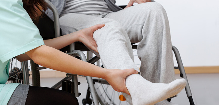 A man in a wheelchair being assisted by a staff member
