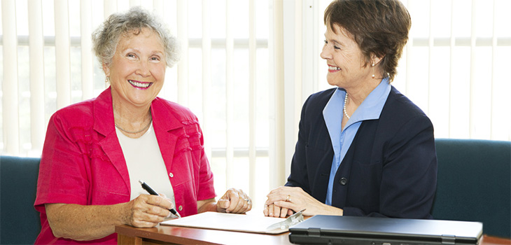 A woman sitting with a staff member going over paperwork