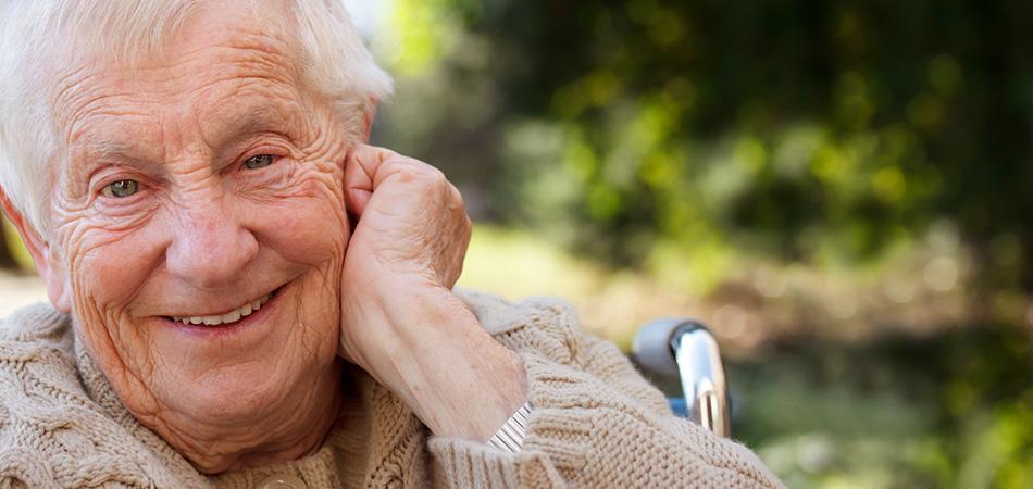 An elderly man smiling in his wheelchair